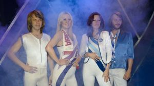 Abban jäsenet tiukoissa esiintymisasuissa savuisella lavalla.