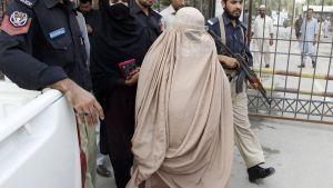Poliisit saattelevat Sharbat Gulaa Peshawarissa, Pakistanissa, 4. marraskuuta.