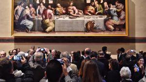 Suuren maalauksen edessä seisoo ihmisiä, joista useat ottavat kuvia kännykällään. maalauksessa on kolmetoista miestä kokoontunut pöydän ympärille. Pöydällä on laseja, lautasia ja valkoinen liina.
