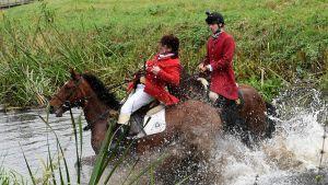 Saksalaiset metsästäjät ylittävät jokea hevosillaan.