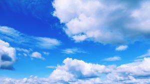 Kuvassa kesäinen maisema, jossa on taivas, pilviä, vettä ja rantaa