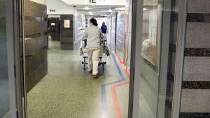 Sairaanhoitaja ja potilas sairaalan käytävällä.