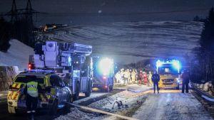Poliisiautoja ja pelastusajoneuvoja yön pimeydessä.