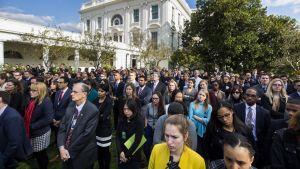 Suuri joukko ihmisiä seisoo hartaan, synkän näköisinä Valkoisen talon pihamaalla. Ilmeet ovat vakavia.