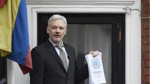 Assange puolikuvassa parvekkeella, kädessään nippu paperia.