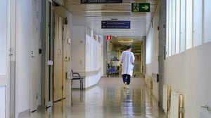Kuva sairaalan käytävästä, jota pitkin kävelee lääkäri