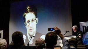 Edward Snowdenin kuva heijastettuna valkokankaalle. Yleisöt kuvaa kännyköillä.
