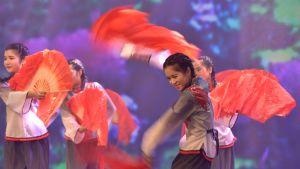 Fouzoun yliopiston kansainvälisen kaupan opiskelijat tanssiesityksessä Kiinan pitkän marssin 80-vuotispäivänä.