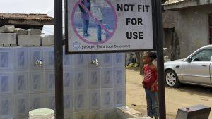 Tyttö katsoo varoituskylttiä, jossa kehoitetaan olla käyttämättä vettä.