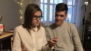 Nuori nainen valkoisessa kauluspaidassa, vieressä istuu nuori mies harmaassa trikoopaidassa.