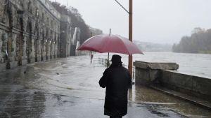 Mies kävelee punaisen sateenvarjon kanssa, Po-joki tulvii rannalle Italiassa.