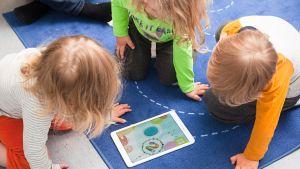 Lapset lattialla olevan tabletin ympärillä