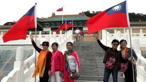 Kiinalaisturistit poseeraavat museon edessä.
