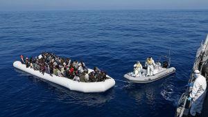 Italian viranomaiset pelastamassa pakolaisia kumiveneestä.
