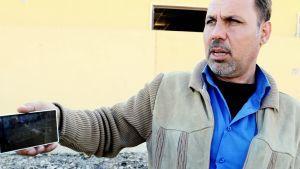 Usama Yasaid näyttää kännykkäänsä.