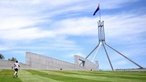Mies juoksee ylös ruohikkorinnettä, taustalla parlamenttitalon valkoisia rakenteita ja salossa liehuva Australian lippu.