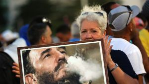 Nainen pitelee valokuvaa nuoresta Fidel Castrosta.