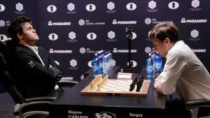 Norjalainen Carlsen miettii silmät kiinni, venäläinen Karjakin tuijottaa lautaa shakin mm-ottelussa.