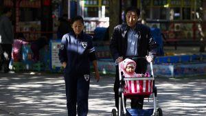 Isoisä työntää pikkulasta rattaissa, nuori nainen kävelee vieressä.