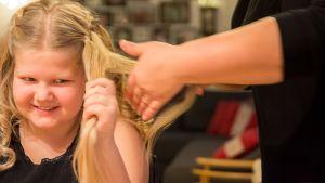 Tytön hiuksia laitetaan kiharalle.