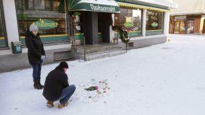 Ihmiset tuovat kyntilöitä ravintola Vuoksenvahdin edustalle sunnuntaina.