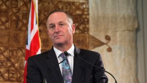 Uuden-seelannin pääministeri maan lipun edessä, katsoo totisena eteenpäin.