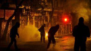 Mielenosoittajia pimeän Ateenan kadulla. Heillä on räjähteitä ja ilotulitteita käsissään.