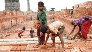 Äiti ja kaksi lasta tekevät työtä alkeellisella tiilitehtaalla. Lapset kantavat tiiliä ja äiti latoo niitä paikoilleen.