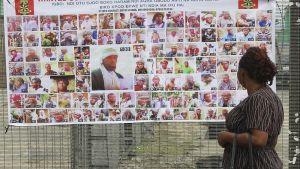Nainen tutkii julistetta, jossa epäiltyjen Boko Haram -terroristien naamakuvia.