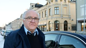 Mauri Vääräniemi taksinsa vierellä Oulun torinrannassa.