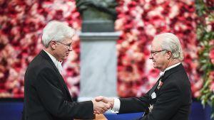 Ruotsin kuningas Kaarle Kustaa XVI luovuttaa talouden Nobel -palkinnon Bengt Holmströmille.