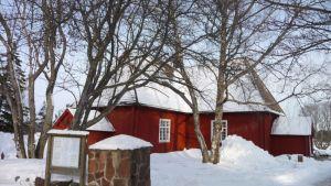 Punainen kirkko lumisessa maisemassa.