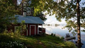 Kesäinen järvimaisema ja rantasauna.