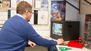 Mies pelaa vanhanaikaista tietokonepeliä