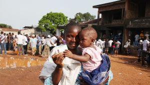 Äiti ja lapsi presidentinvaalien äänestyspaikan edustalla Free Townissa, Sierra Leonessa, marraskuussa 2012.