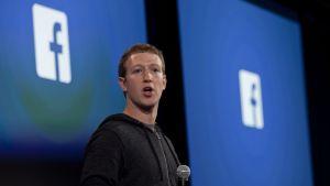 Mark Zuckerberg puhuu mikrofoni kädessään. Taustalla näkyy Facebookin logo.