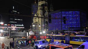 Ambulansseja ja pelastushenkilökuntaa tapahtumapaikalla kirkon juurella. On pimeää.