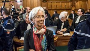 Lagarde oikeudessa, taustalla oikeuden henkiökuntaa, toimittajia.