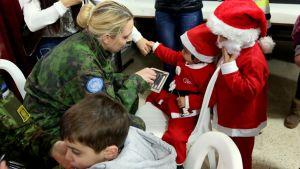 Nainen maastokuvioisessa puvussa sekä kaksi joulutontuiksi pukeutunutta lasta.