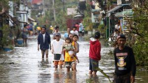 Useita ihmisiä kävelee tulvivalla kadulla. Vesi ulottuu ihmisiä säären puoliväliin.