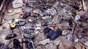 Useita lenkkitossuja ja muita tavaroita hiekalla tsunamin jälkeen.