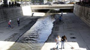 Ihmiset putsaavat Barada-joen kanavaa Damaskoksessa