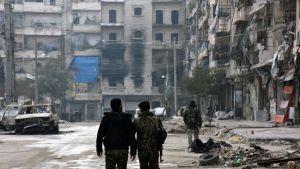 Sotilaita ja Aleppon raunioita