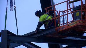 Rakentaja nostaa palkkia tehdastyömaalla.