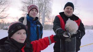 Harri Väänänen pitelee kädessään isoa ilotulitetta. Vierellä pojat Severi (vas.) ja Hermanni.