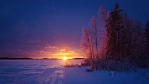 Aurinko nousee talvisen järven takaa.