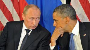 Putin katsoo Obamaa, joka näyttää katsovan vähän ohi. Istuvat vierekkäin.