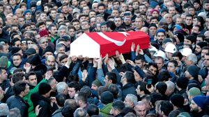 Suuri ihmisjoukko kantaa arkkua, joka on päällystetty Turkin lipulla.