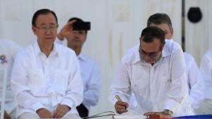 Ban Ki-moon istuu vieressä, kun Rodrigo Londono Echeverri allekirjoittaa sopimusta. Taustalla näkyy muita ihmisiä. Kaikki ovat pukeutuneet valkoiseen.