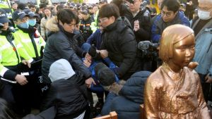Käsirysyä, toimittajia ja poliiseja, etualalla nuorta naista esittävä patsas.